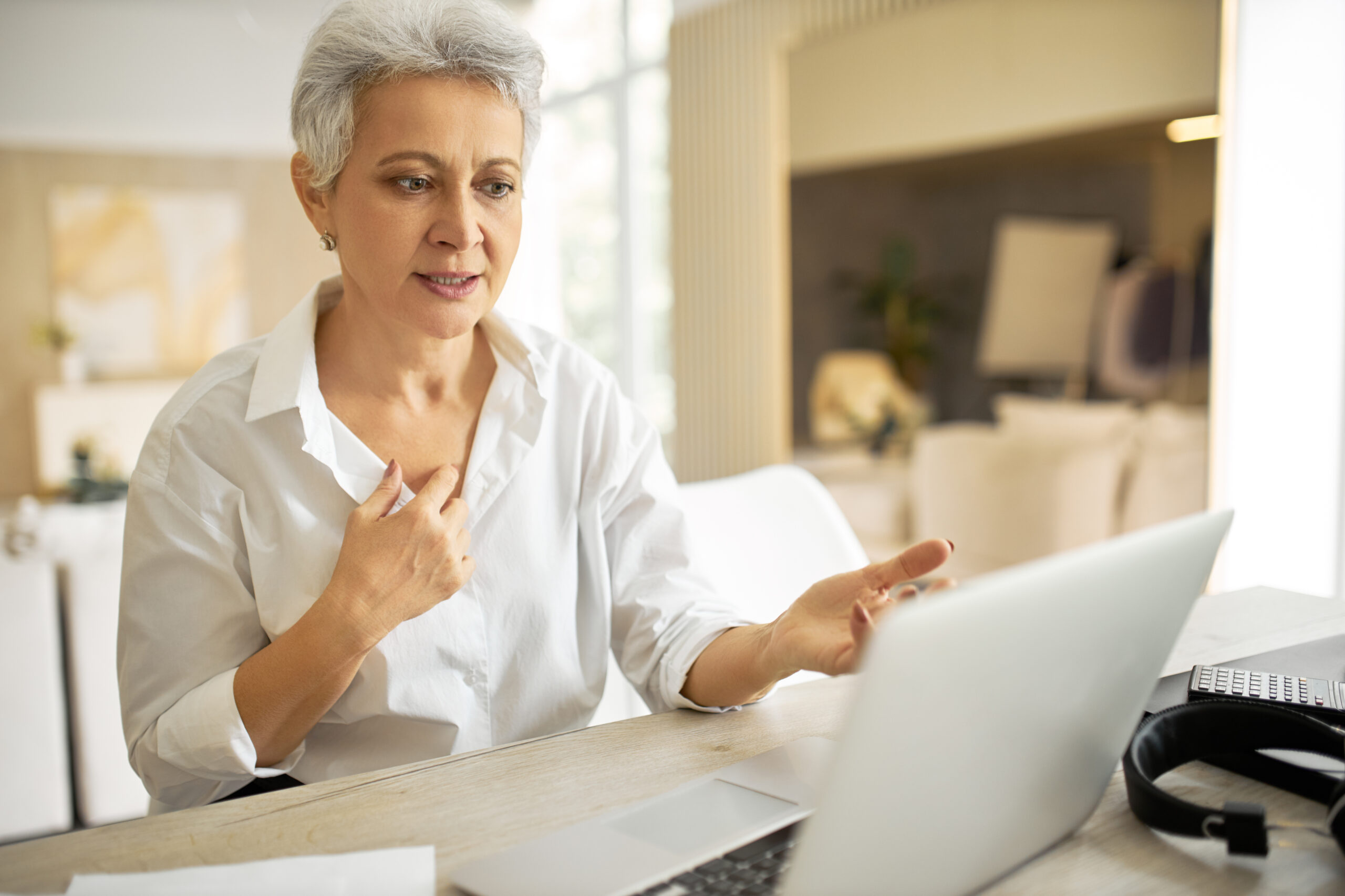 People, technology and communication concept. Serious middle aged female manager with gray hair sitting at table in front of portable computer, sharing her ideas with colleagues during video call