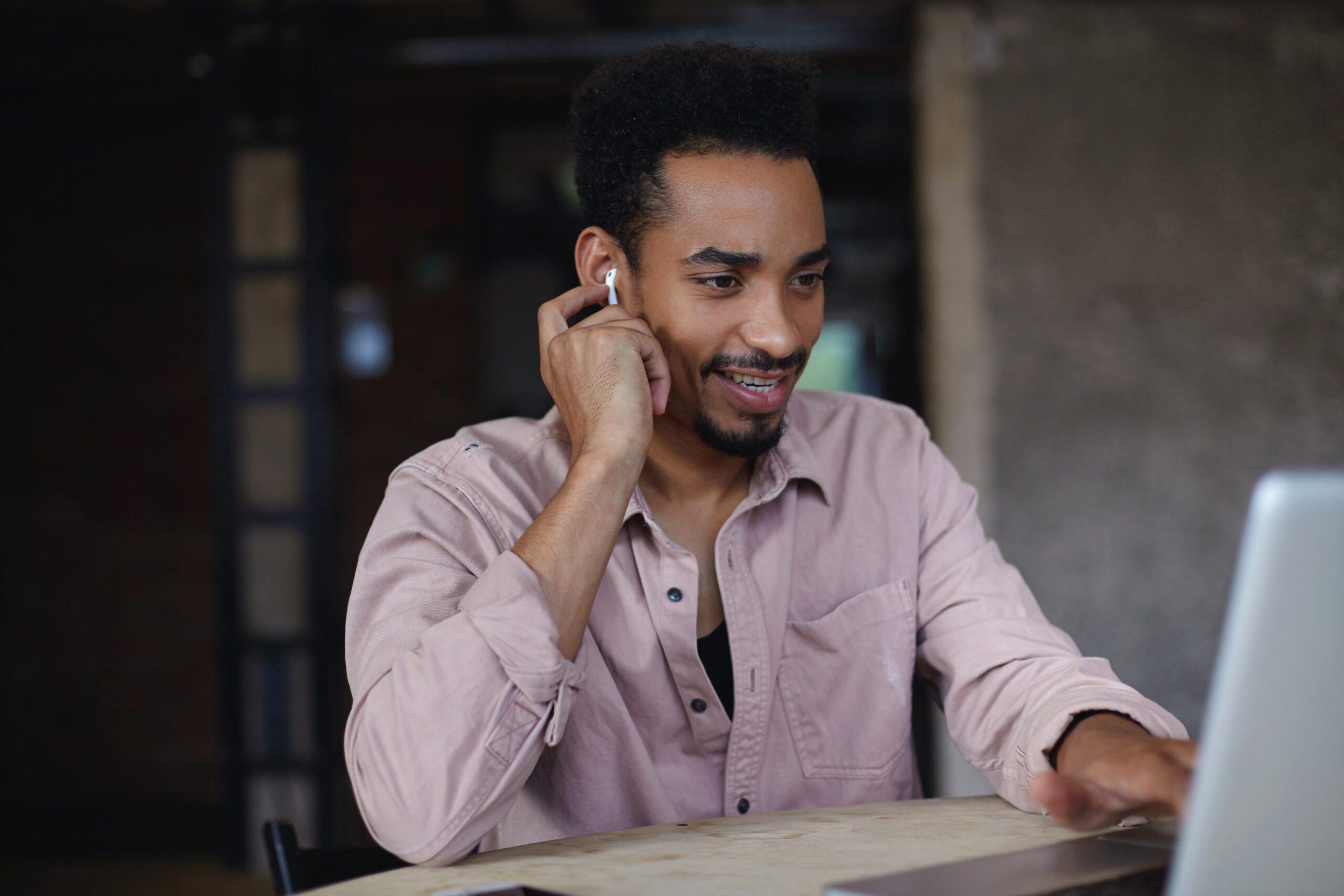 Indoor shot of cheerful young dark skinned bearded man in beige shirt sitting over modern office interior and having video call with laptop, smiling slightly and keeping hand on earpiece in his ear